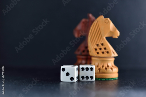 Two white dice and chess knights ob black плакат