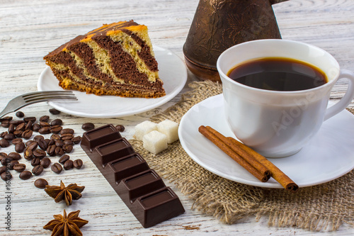 Spoed canvasdoek 2cm dik Chocolade Delicious chocolate cake on a plate with a cup of coffee . Coffee beans, a piece of chocolate, anice, sugar and cinnamon sticks on wooden table