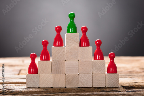 Green And Red Pawn Figurines Arranged On Wooden Blocks