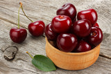 cherries in bowl on old wooden background