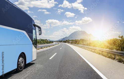 Fototapeta Bus rushes along the asphalt high-speed highway.