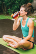 Tired woman drinking water after training
