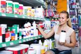 Portrait of adult female customer taking bottle