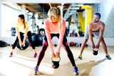 Young group having functional fitness training with a kettlebell in sports gym.