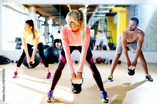 Sticker Young group having functional fitness training with a kettlebell in sports gym.