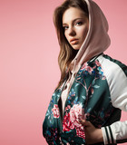 Portrait of a stylish girl in a bomb jacket with floral print standing on a pink background - 167448307