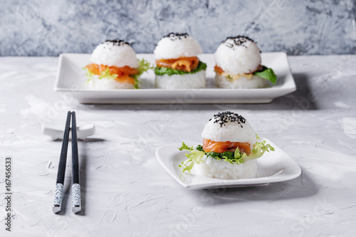 Mini rice sushi burgers with smoked salmon, green salad and sauces, black sesame served on white square plate with chopsticks over gray concrete background Poster