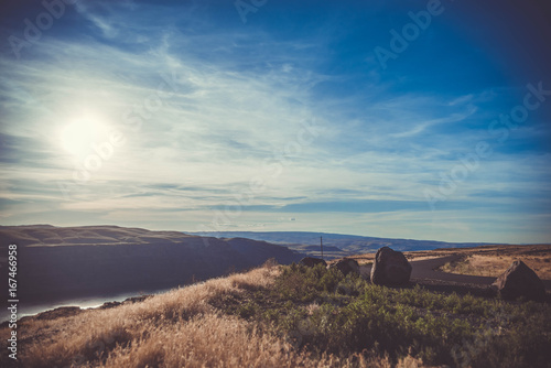 Beautiful sunset or sunrise in mountains taken on a grassy hill with a dramatic sky, clouds, sun and rocks.