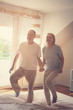 Quadro Senior couple dancing and jumping together on bed  holding hands.