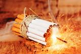Rauch Stopp / einige zusammengebundene Zigaretten auf hölzernem Untergrund, in der Mitte brennt eine Wunderkerze - 167483118