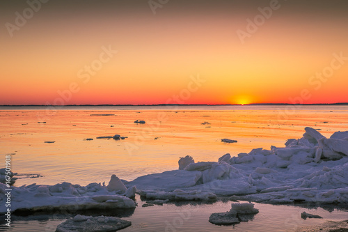 orange Sunrise over Chesapeake Bay Maryland in winter after ice buildup