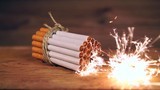 Guter Vorsatz, aufhören zu rauchen / zusammengebundene Zigaretten auf hölzernem Untergrund, mittig brennt eine Wunderkerze, Zeitlupe ohne Ton - 167502779
