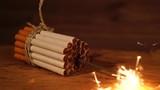 Guter Vorsatz, aufhören zu rauchen / zusammengebundene Zigaretten auf hölzernem Untergrund, mittig brennt eine Wunderkerze, Zeitlupe ohne Ton - 167503512