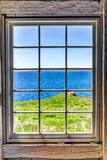 Patrz? C przez stare okna dom z urwiska i widokiem na ocean w Bonaventure Island, Quebec, Kanada
