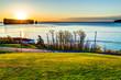 Famous Rocher Perce rock in Gaspe Peninsula, Quebec, Canada, Gaspesie region with cityscape at sunrise and sun