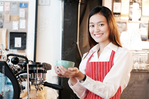 Wall mural Young asian women Barista holding coffee cup with smiling face at cafe counter background, small business owner, food and drink industry concept