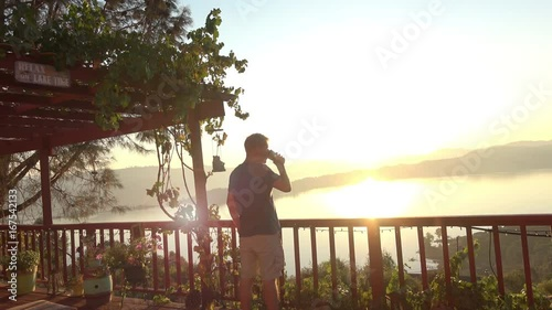 Morning Sunrise View. Adult Male on a Terrace Deck with an Amazing Panoramic View is Enjoying a Cup of Coffee. Shot in Lake County California.