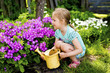Quadro The girl with a watering can in a garden