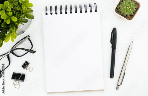 White office desk table with blank notebook page and supplies Poster