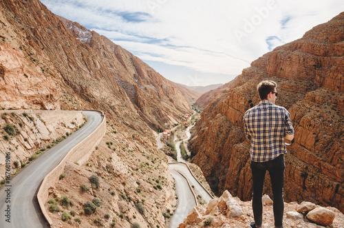 Foto op Canvas Marokko Schlucht in Marokko mit gewundener Straße und Mann im Vordergrund