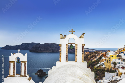 The bell tower of Greek Orthodox Church on the background waters of the Aegean sea in Oia town on Santorini island in Greece