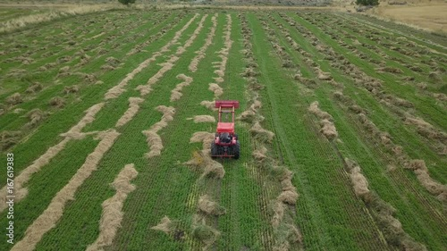 Poster Aerial follow farm tractor working hay in field. Aerial rural farming community agricultural economy. Spring summer weather mountain valley green agriculture field. Seasonal rural farm harvest.