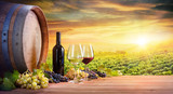 Wine Glasses And Bottle With Barrel In Vineyard At Sunset - 167619924