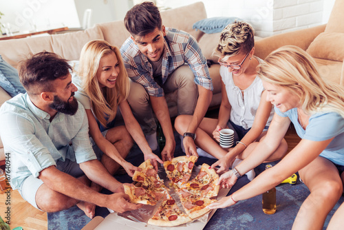 Happy friends eating pizza at home - 167640944