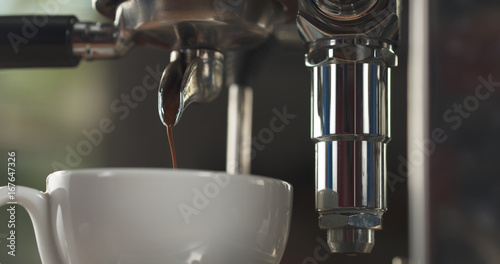 Wall mural coffee pour from professional coffee machine into cappuccino cup