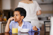 little mixed race boy pondering while eating breakfast with mother in background - 167648719