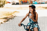 Portrait of a beautiful young girl in a hat with a bicycle on city background