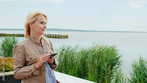 A young woman is walking around the lake, using a mobile phone. Lake Balaton in Hungary. Steadicam shot