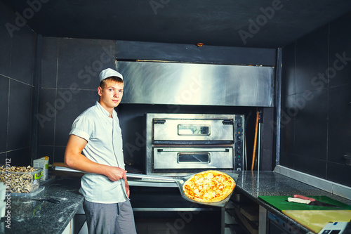 Foto op Plexiglas Pizzeria The cook keeps a big pizza