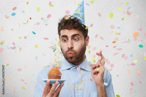 Juliste Attractive man who is celebrating his birthday, blowing out candle on cupcake, crossing his fingers while making wish