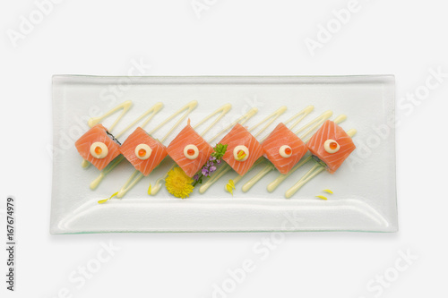 Salmon sushi rolls in glass plate on white background