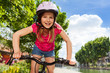 Happy girl in safety helmet cycling at city park