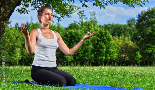 Wall mural Young woman during yoga meditation in the park