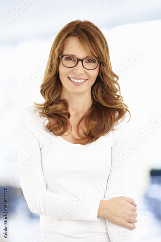 Smiling businesswoman portrait. Shot of an attractive middle aged businesswoman standing at the office.