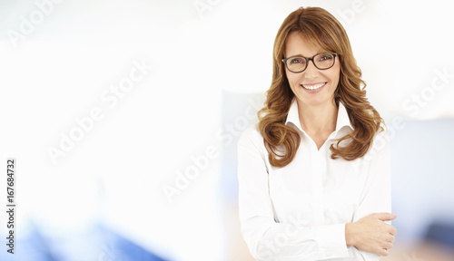 Fridge magnet Smiling businesswoman portrait. Shot of an attractive middle aged businesswoman standing at the office.