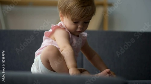 Pleasant cute toddler resting on the couch