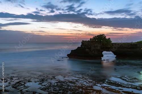 Sunset near famous tourist landmark of Bali island - Tanah Lot & Batu Bolong temple. Long exposure effect, Bali Indonesia. Tropical nature landscape of Indonesia, Bali.
