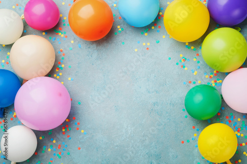 Foto Murales Colorful balloons and confetti on blue table top view. Festive or party background. Flat lay style. Copy space for text. Birthday greeting card.