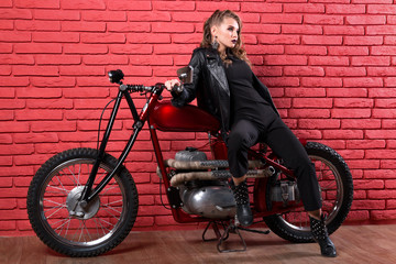 Coveted woman or girl in a leather jacket and tight pants, boots sits on a motorcycle, with an unusual hairdo and make-up on a brick red wall