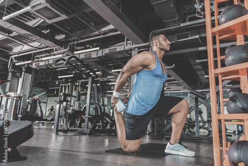 Serene unshaven man practicing sport in gym