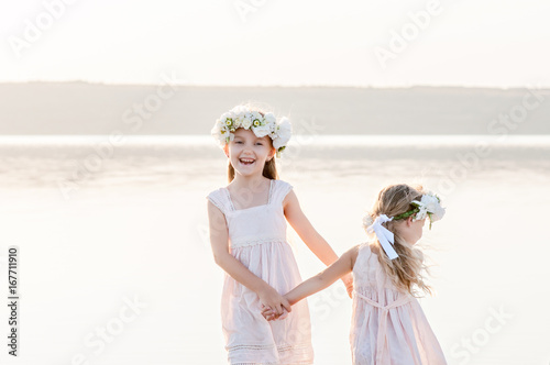 Beautiful sisters hold hands and dance on water in dresses and laugh