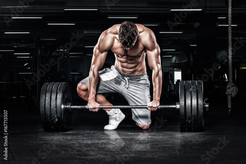 Sticker Muscular young fitness sports man workout with barbell in fitness gym