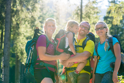 Family with two daughters on hike in the woods backlit in summer - 167716113