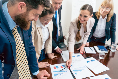 Fridge magnet Multi-ethnic team of five dedicated specialists smiling while analyzing various charts with positive statistics about the profit and the development of the company