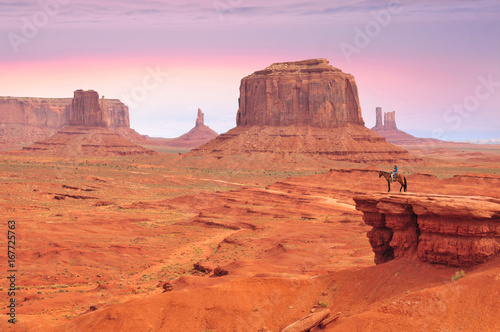 Foto op Canvas Koraal Man on a horse, view from John Ford's Point in Monument Valley with the West Mitten Butte and the Merrick Butte in Utah-Arizona border, United States of America.