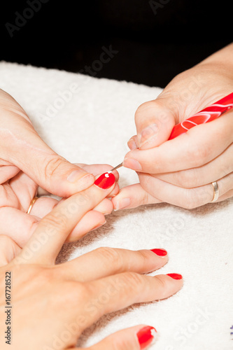 The esthetician decorates with flowers the nails of the hands of the client